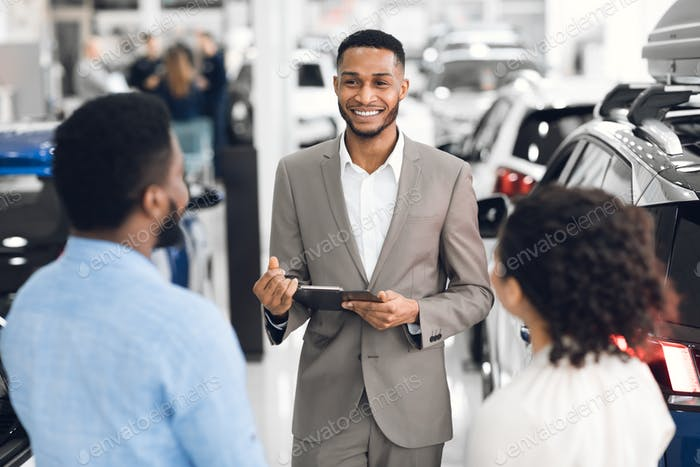Salesman In Car Dealership Talking With Customers Helping Choose Auto