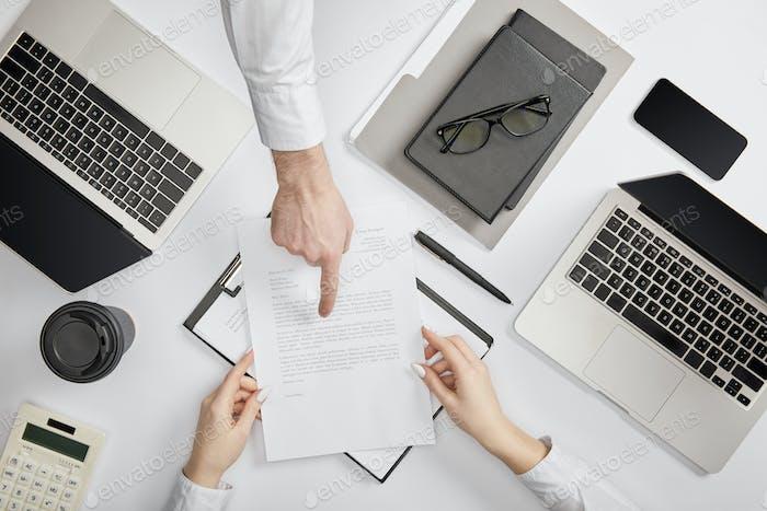Draufsicht eines Geschäftsmannes, der auf einen Vertrag zum Angestellten verweist