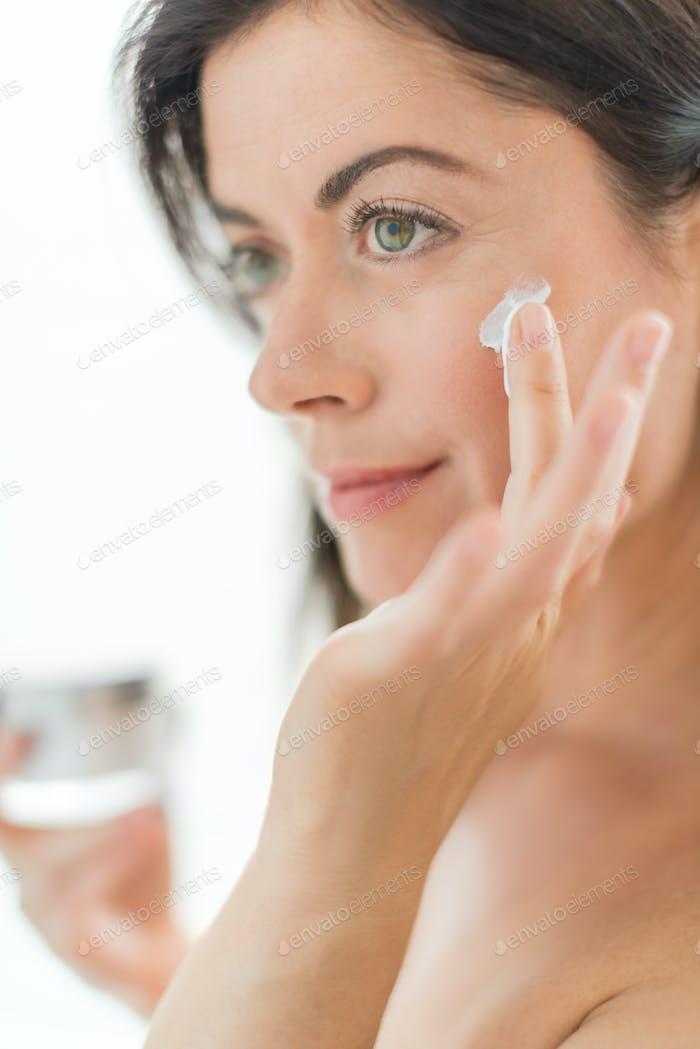 woman in her forties applying cream
