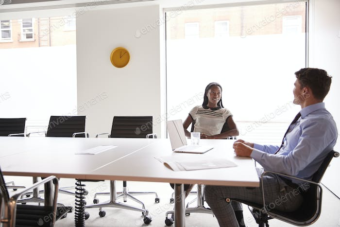 Businessman And Businesswoman Having Discussion Around Boardroom Table In Meeting Room