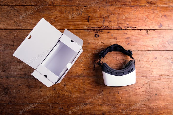 Virtual reality goggles with paper box on wooden table
