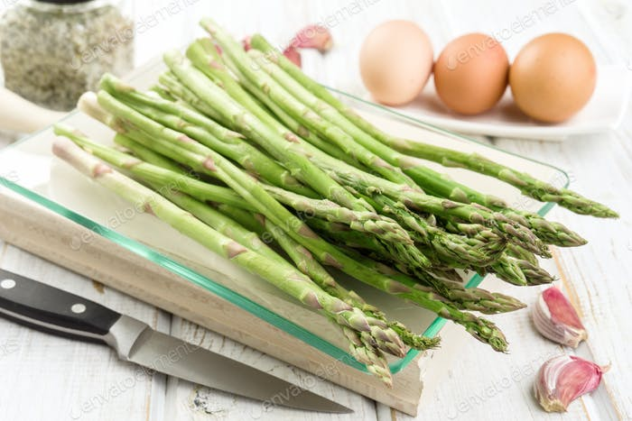 bunch of asparagus uncooked on modern wooden stage with other cooking ingredients