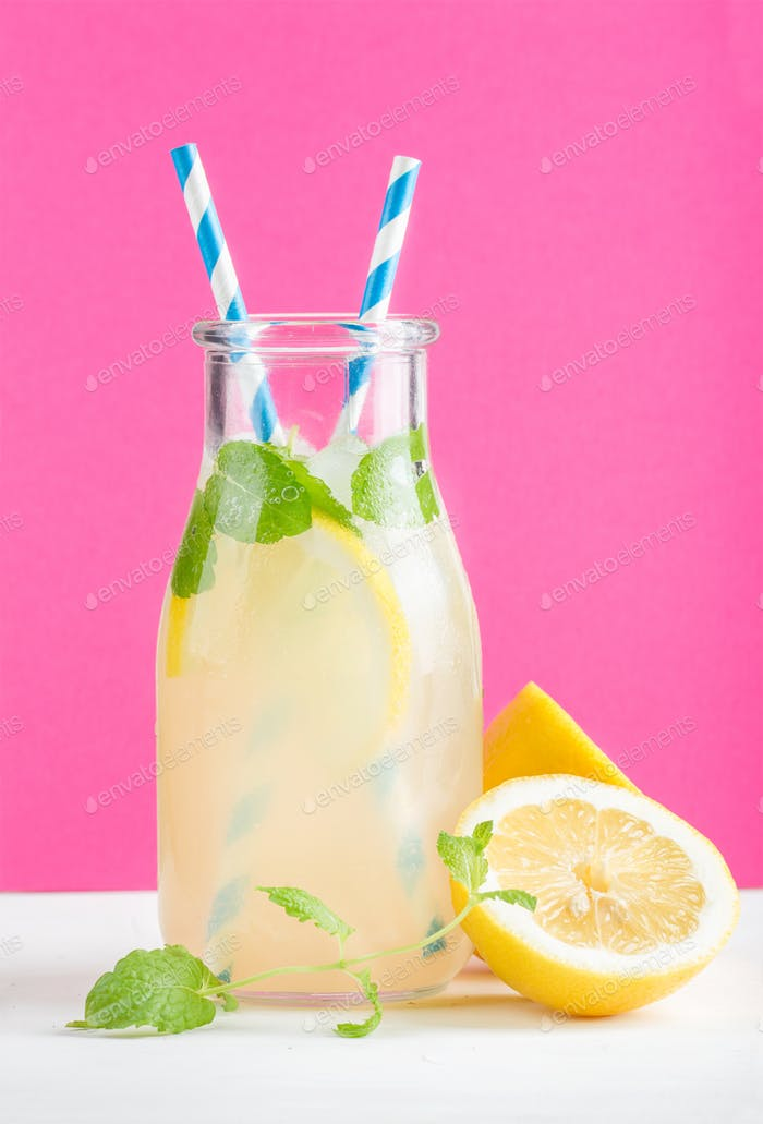 Bottle of homemade lemonade with mint, ice, lemons, paper straws and bright purple background