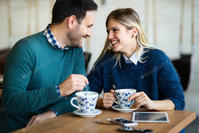 Young beautiful couple having date in coffee shop