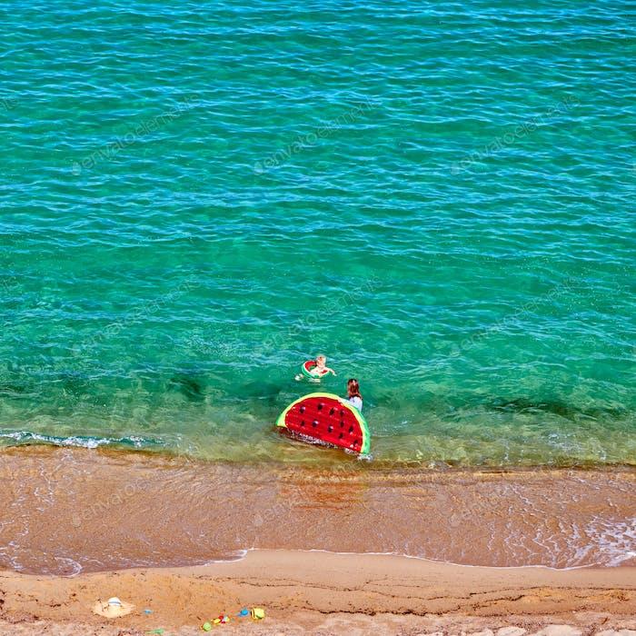 Junge und seine Mutter am Strand mit aufblasbarem Schwimmer