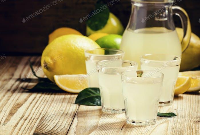 Home lemon liqueur and fresh lemons and limes