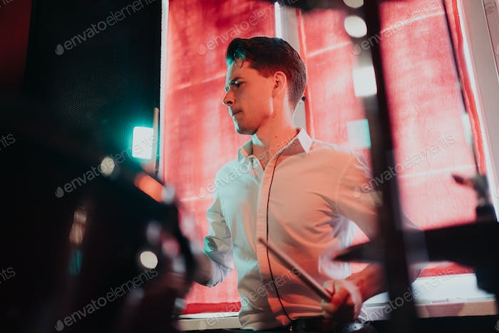 Handsome talented guy play on drums preparing for concert