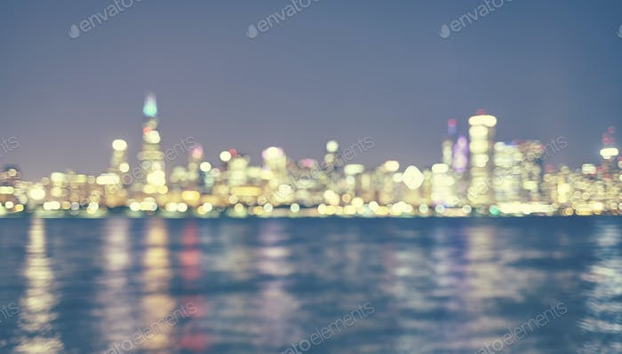 Vintage toned blurred Chicago city lights with reflection in Lak