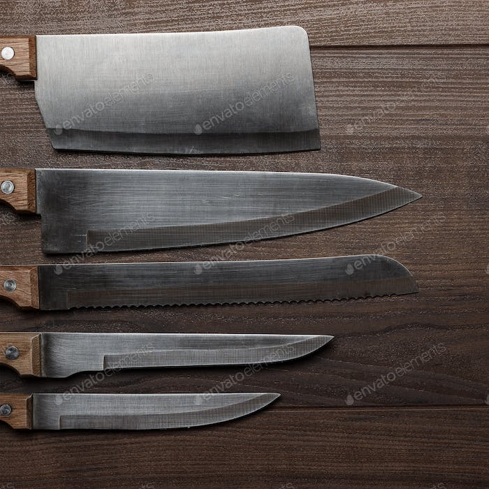 Kitchen Knifes On The Brown Wooden Background