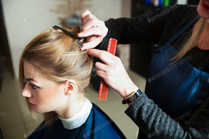 Hairdresser prepares for work with young woman.