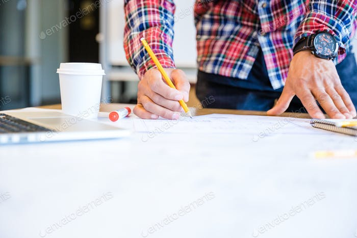 Young african american student drawing blueprint with pencil
