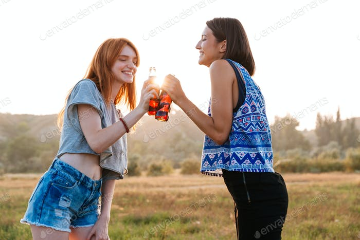 Two cheerful women drinking soda and having fun outdoors