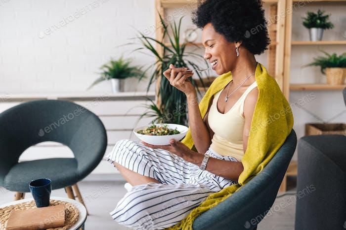 Hermosa mujer afroamericana comiendo ensalada de verduras en casa