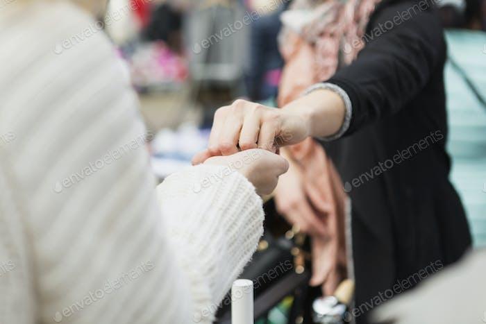 Продавец даёт что-то женщине на блошином рынке