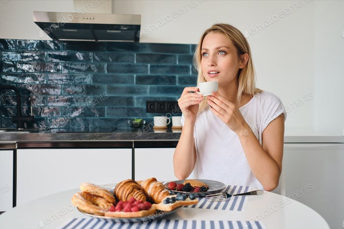 Young attractive blond woma dreamily looking aside with cup of coffee at the table with breakfast