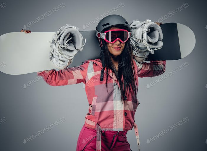 A woman with snowboard in a studio on grey background.