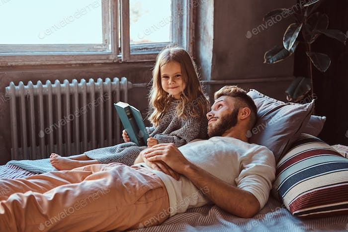 Handsome young father and daughter reading storybook together while lying on bed.