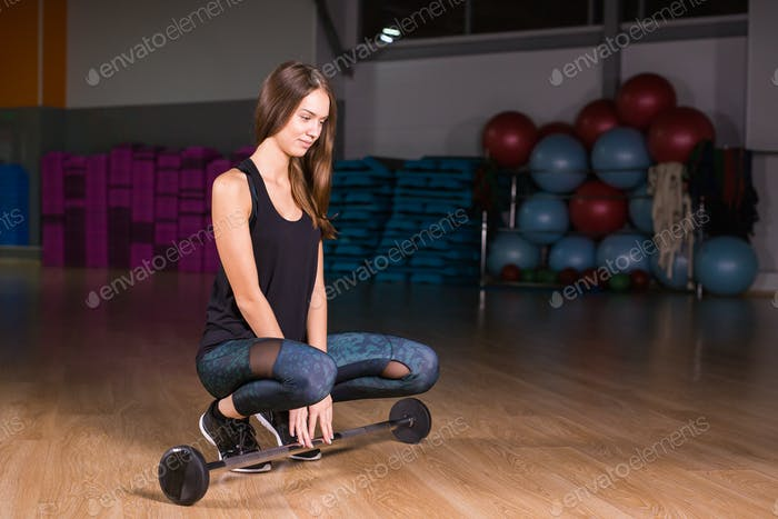 Young fitness woman with barbell in gym