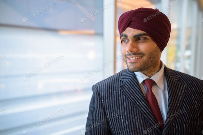 Happy Indian businessman with turban looking through window