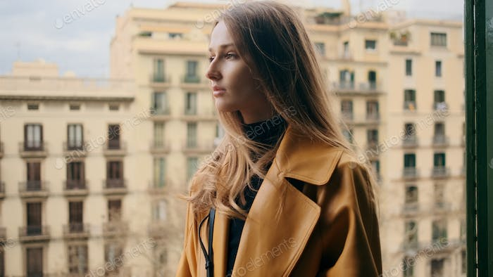 Gorgeous girl thoughtfully looking away on balcony with beautiful view on architecture