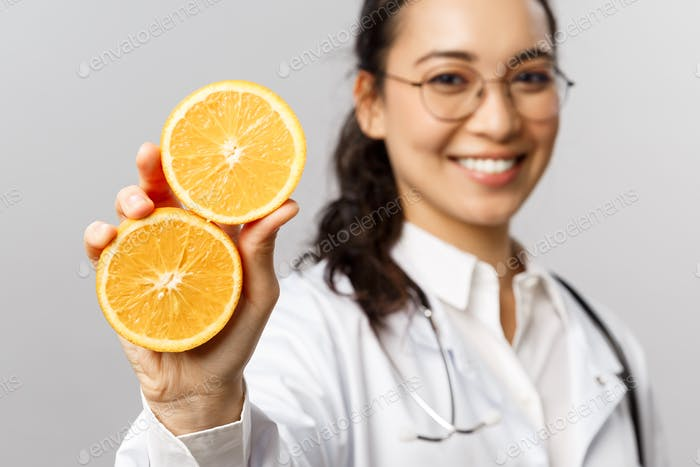 Close-up portrait of asian female doctor, therapist showing pieces of orange and smiling, give