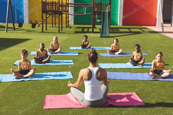 Caucasian trainer teaching yoga to students on yoga mat in school playground at schoolyard
