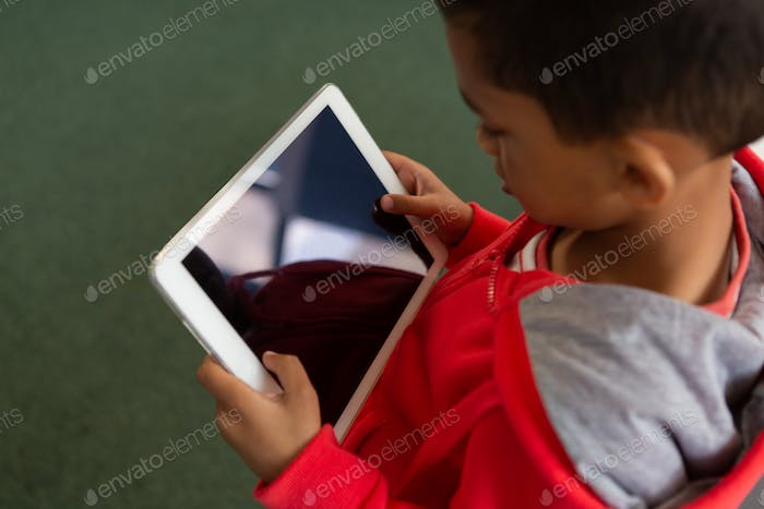 Cute schoolboy using digital tablet in a classroom at elementary school