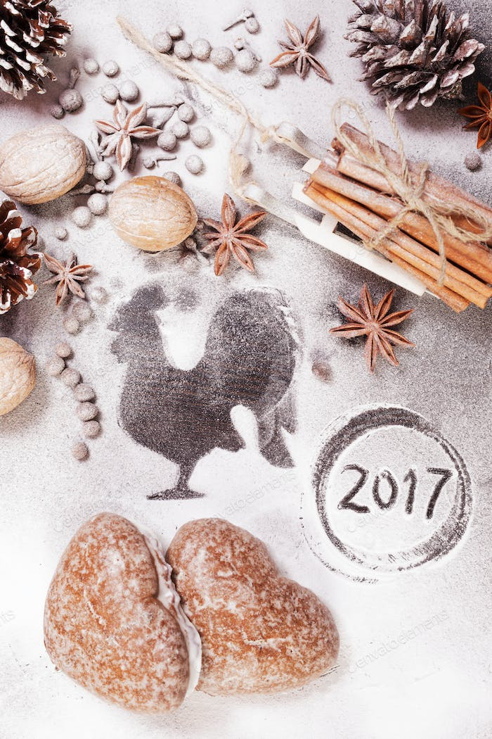 New year flat background with cones, rooster silhouette, spices  and gingerbread