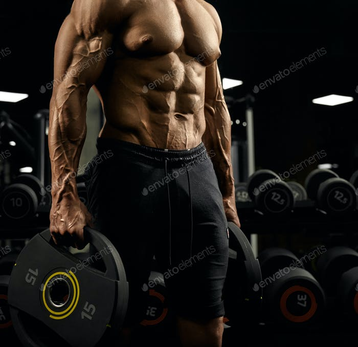 Tensed male bodybuilder holding weights