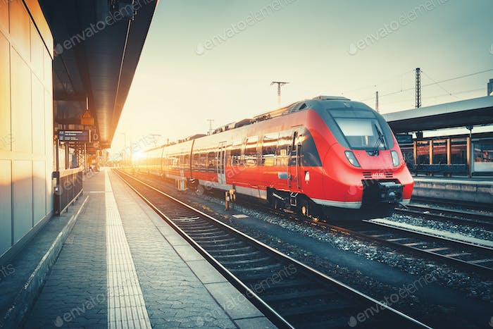 Railway station with beautiful modern red commuter train at suns
