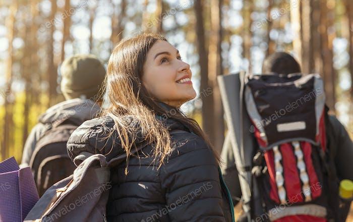 Three tourists hiking in autumn woods, girl looking around