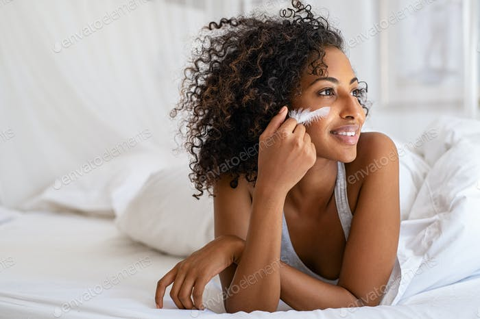 Woman feeling her soft skin on bed