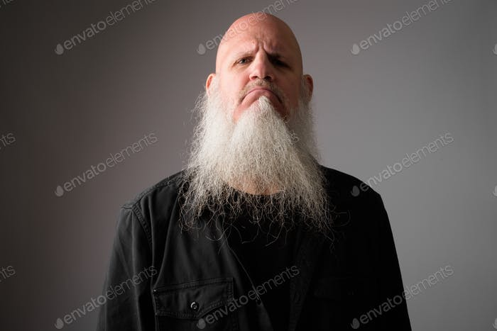 Face of mature bald bearded man looking angry