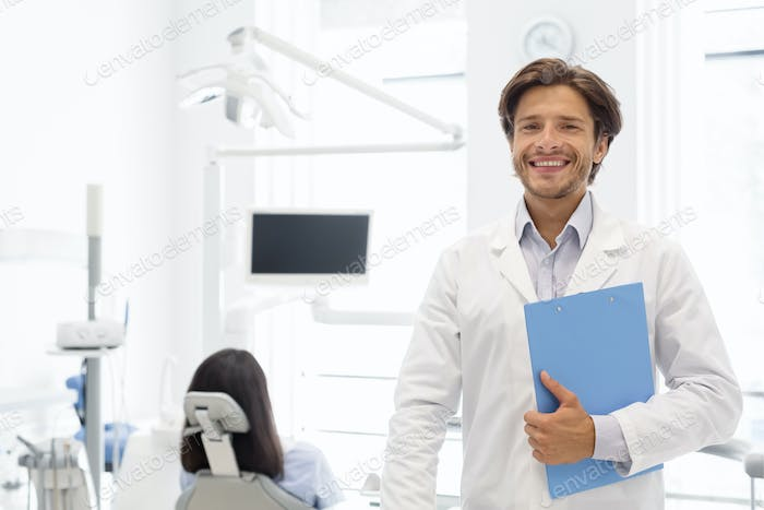 Delighted dentist smiling and holding folder in dental cabinet