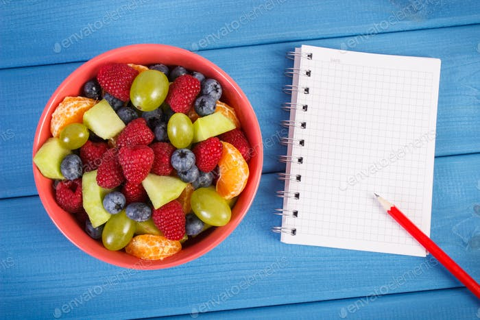 Fruit salad and notepad for writing notes, healthy lifestyle and nutrition concept