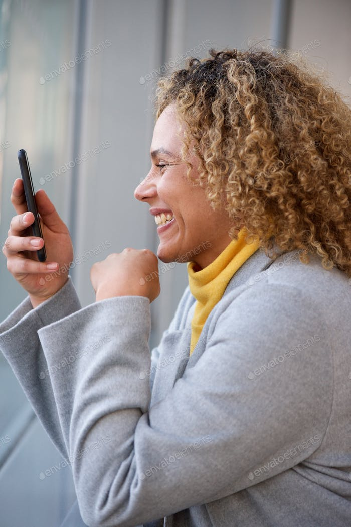 happy african american woman with curly hair looking at mobile phone