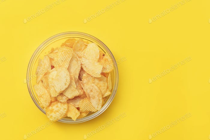 Crispy potato chips in glasses bowl on yellow background, top view