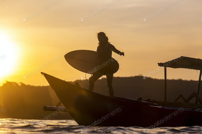 Surfer in ocean at sunset time