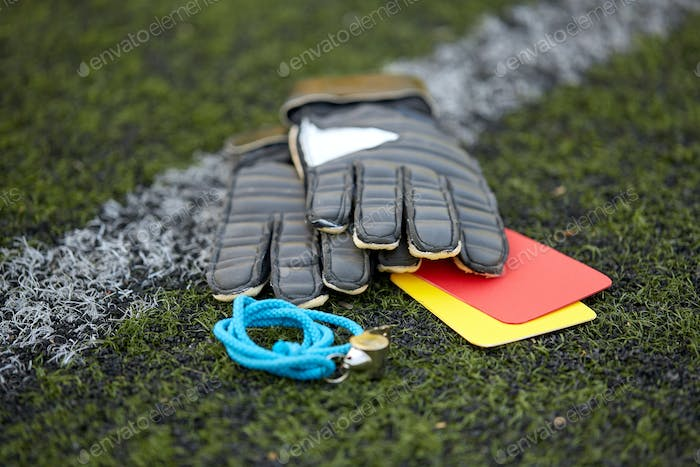 gloves, whistle and caution cards on soccer field