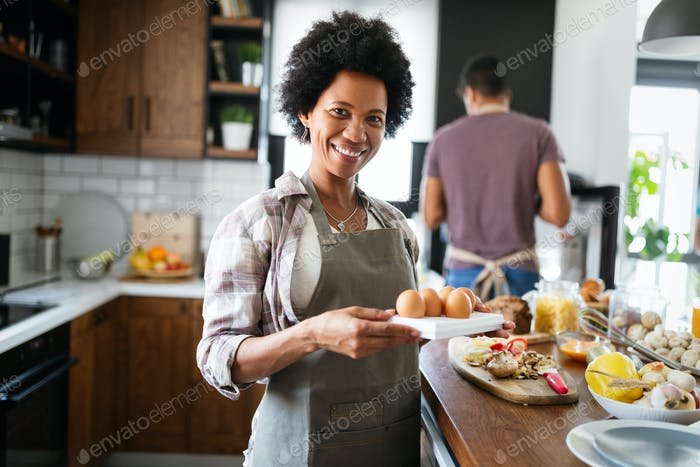Happy black couple cooking and tasting healthy food in kitchen