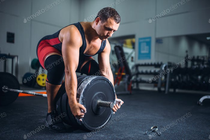 Male powerlifter prepares a barbell in gym