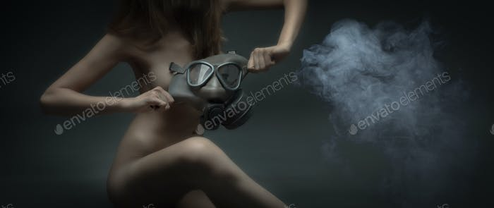 Naked woman with gas mask and poisonous smoke