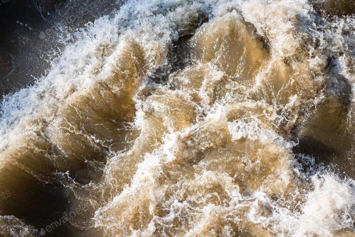 Close up at fast foaming and mudy river