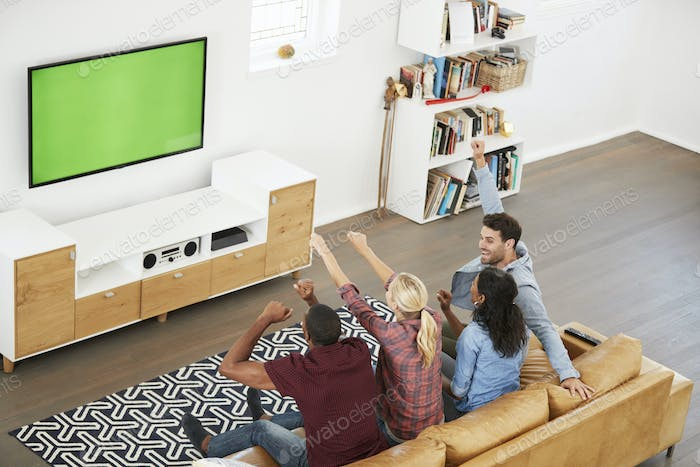 Group Of Young Friends Watching Sports On Television And Cheering