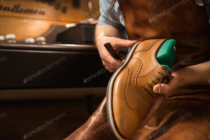 Shoemaker in workshop making shoes.