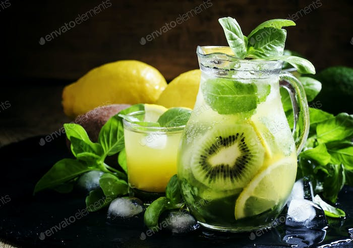 Refreshing summer cocktail with green basil, lemon, kiwi fruit and ice in a jug