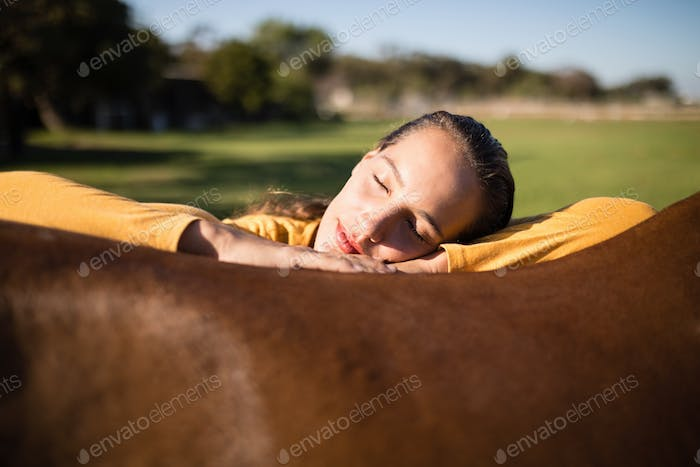 Female jockey relaxing on horse at barn