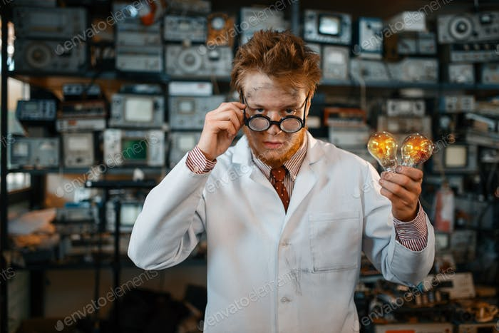 Strange engineer holds electric lamp in laboratory