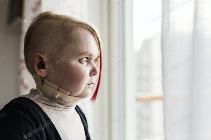 Portrait of disabled young woman looking through window