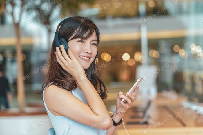 Asian woman using smart mobile phone and listening the music via Head cover headphones
